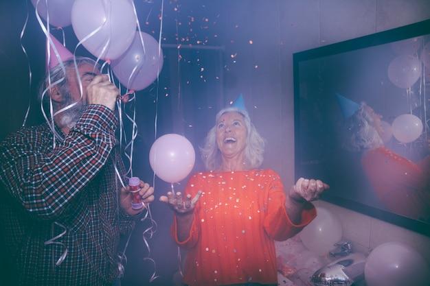 Sorrindo, homem sênior, soprando, bolha, varinha, e, dela, esposa, jogar, confetti, em, a, partido aniversário Foto gratuita