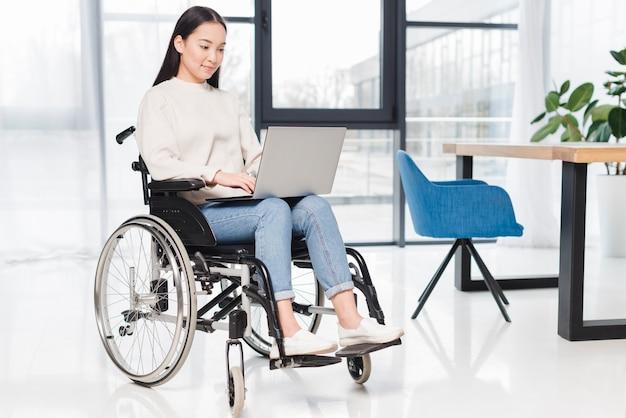 Sorrindo, incapacitado, mulher jovem, sentando, ligado, cadeira rodas, usando, laptop, em, escritório Foto gratuita