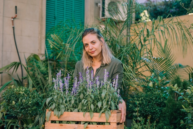Sorrindo, jardineiro, carregar, lavanda, potenciômetros flor, em, crate, em, plante berçário Foto gratuita