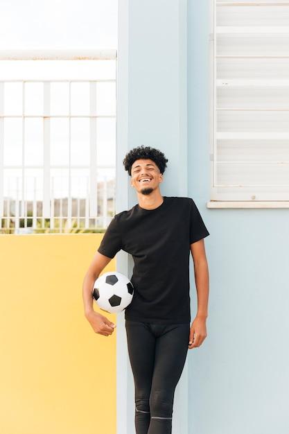Sorrindo, jogador de futebol, segurando bola, e, olhando câmera Foto gratuita