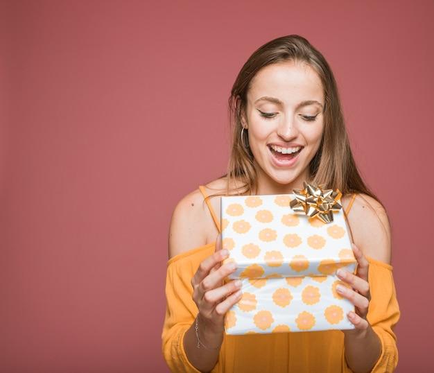 Sorrindo jovem abrindo a caixa de presente floral com laço dourado Foto gratuita