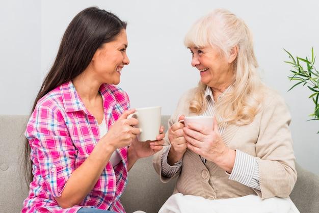 Sorrindo, jovem, adulto sênior, mãe, segurando, xícara café, olhando um ao outro Foto gratuita