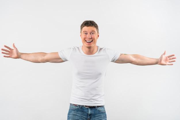 Sorrindo jovem bonito outstretching seus braços isolados no fundo branco Foto gratuita