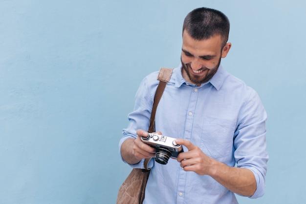 Sorrindo jovem carregando mochila e olhando para a câmera em pé perto da parede azul Foto gratuita