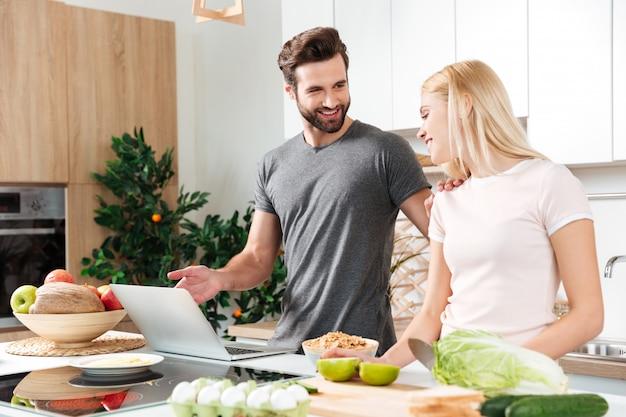 Sorrindo jovem casal apaixonado, cozinhando juntos usando laptop Foto gratuita