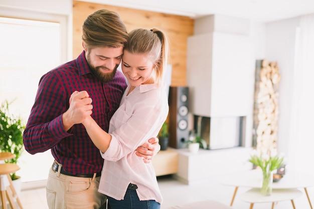 Sorrindo jovem casal dançando Foto gratuita