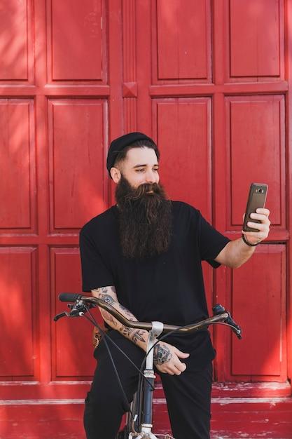 Sorrindo, jovem, ciclista, levando, selfie, ligado, seu, smartphone, frente, portas vermelhas Foto gratuita