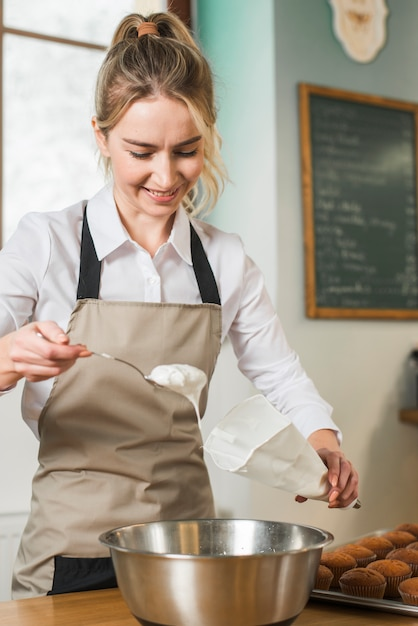 Sorrindo jovem colocar creme branco no saco de confeiteiro branco Foto gratuita