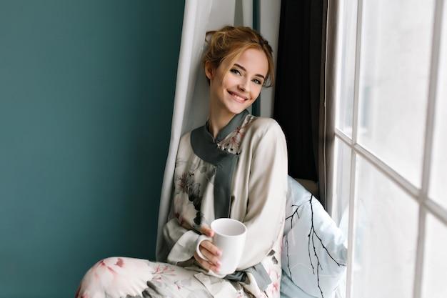Sorrindo jovem com uma xícara de café, chá em seu tinha, sentado no parapeito da janela, bom dia relaxe. vestindo pijama de seda com flores, tem cabelos loiros. foto em cores turquesas. Foto gratuita