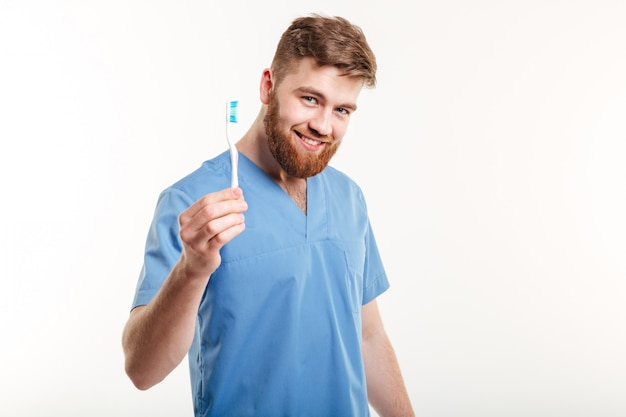 Sorrindo jovem dentista masculina segurando a escova de dentes Foto gratuita