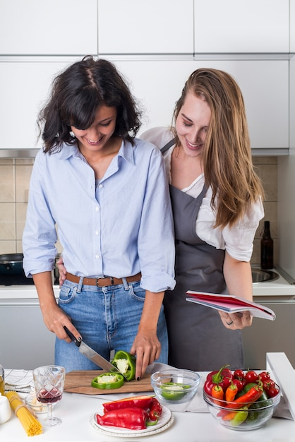 Sorrindo jovem e sua amiga preparando comida na cozinha Foto gratuita