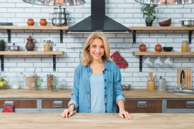 Sorrindo jovem em pé atrás da mesa de madeira na cozinha Foto gratuita