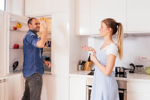 Sorrindo jovem em pé perto da geladeira aberta jogando vegetais na mão da sua esposa Foto gratuita