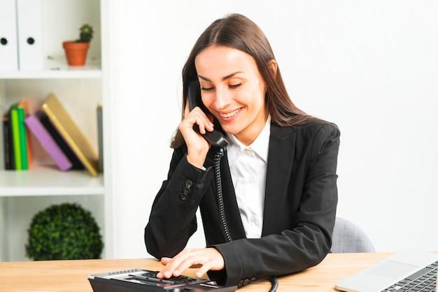 Sorrindo, jovem, executiva, conversa telefone, em, escritório Foto gratuita