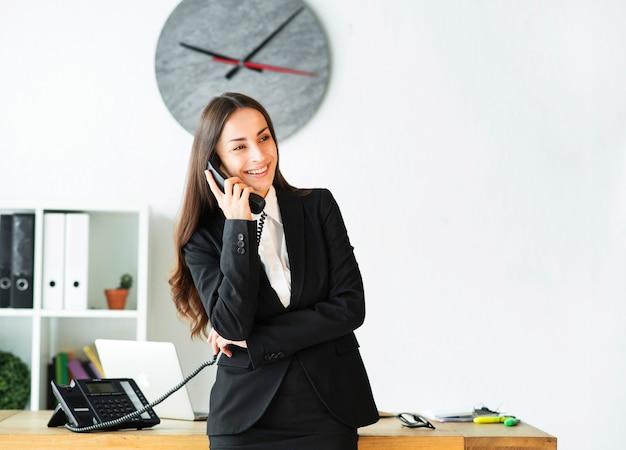 Sorrindo, jovem, executiva, ocupado, falando, telefone, escritório Foto gratuita