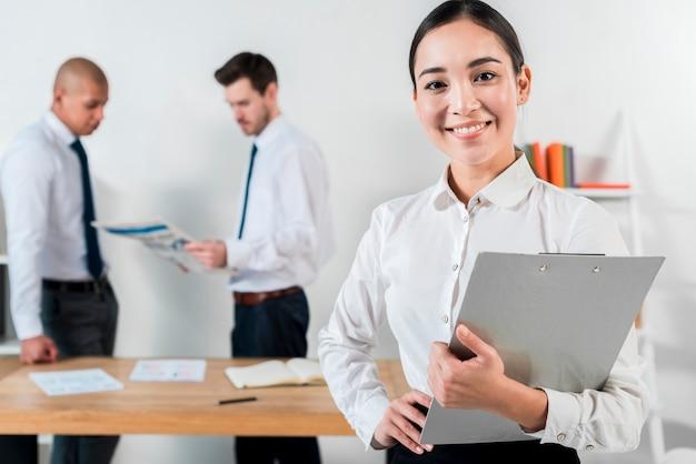 Sorrindo, jovem, executiva, segurando clipboard, em, mão, com, dois, homem negócios, trabalhando, em, fundo Foto gratuita