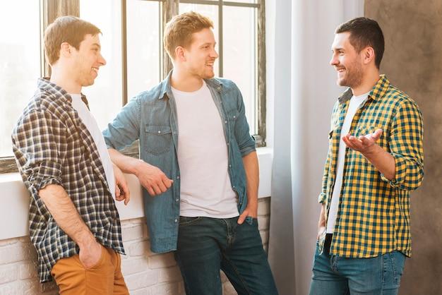 Sorrindo jovem falando com seus amigos perto da janela Foto gratuita