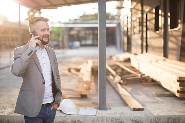 Sorrindo jovem falando no celular no canteiro de obras Foto gratuita