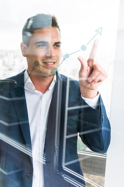 Sorrindo, jovem, homem negócios, apontar dedo, em, aumentando, gráfico, ligado, vidro transparente Foto gratuita