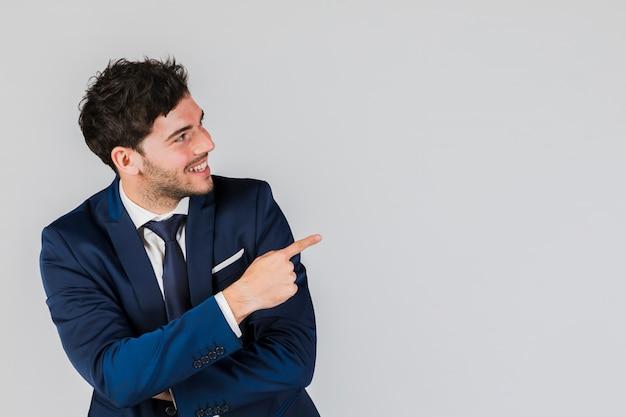 Sorrindo, jovem, homem negócios, apontar, seu, dedo, contra, experiência cinza Foto gratuita