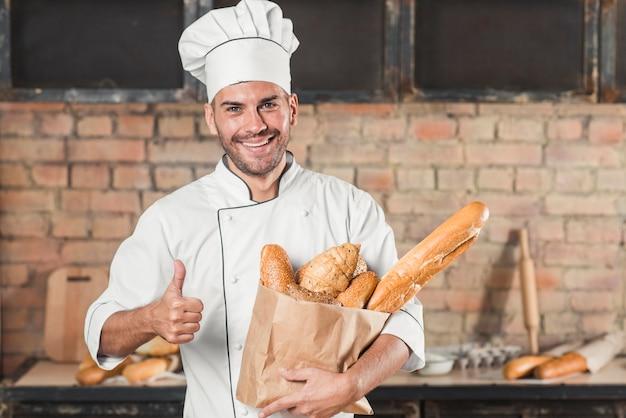 Sorrindo, jovem, macho, padeiro, segurando, loaf, de, pães, em, saco papel, mostrando, polegar, sinal Foto gratuita