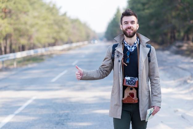 Sorrindo, jovem, macho, turista, com, câmera vintage, ao redor, seu, pescoço, hitchhiking, ao longo, um, estrada Foto gratuita