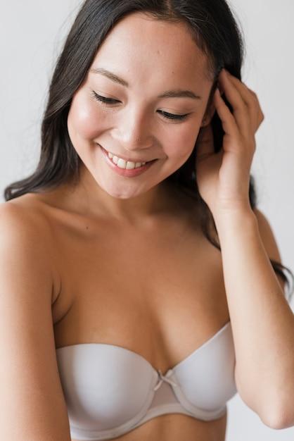 Sorrindo jovem morena asiática em sutiã tocando o cabelo Foto gratuita