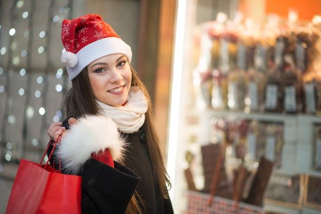 Sorrindo jovem mulher às compras em uma cidade antes do natal Foto Premium