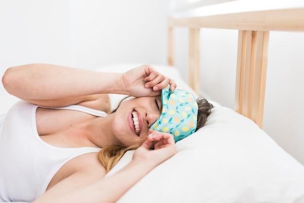 Sorrindo jovem mulher dormindo na cama com uma máscara de olho Foto gratuita