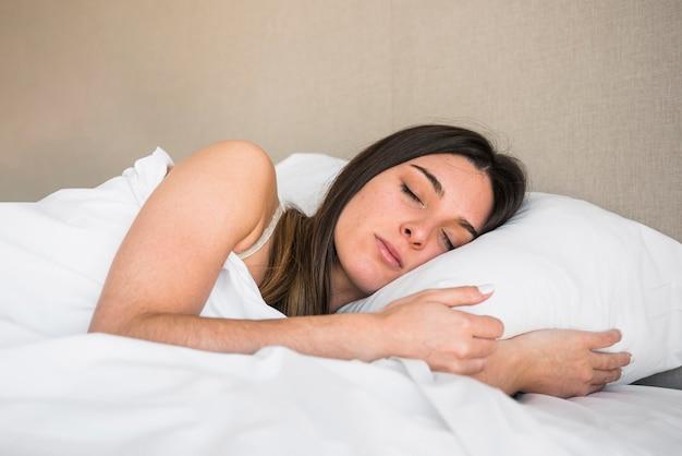 Sorrindo jovem mulher dormindo na cama contra o pano de fundo colorido Foto gratuita