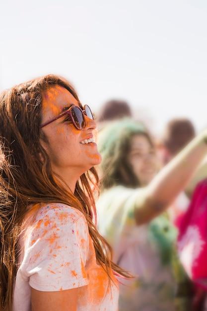 Sorrindo jovem mulher usando óculos de sol bagunça com um pó de holi laranja Foto gratuita