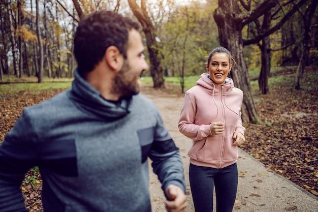 Sorrindo jovem positivo no sportswear, competindo com sua namorada e ganhando. aptidão no conceito de natureza. Foto Premium