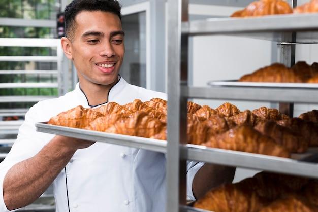 Sorrindo jovem removendo a bandeja de croissant de cozimento da prateleira Foto gratuita