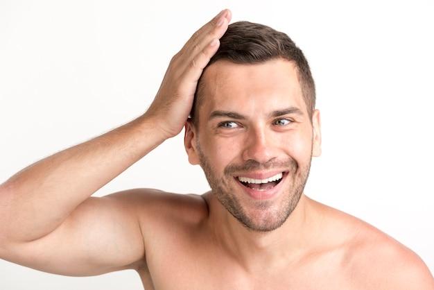 Sorrindo jovem sem camisa tocando seu cabelo sobre o pano de fundo branco Foto gratuita