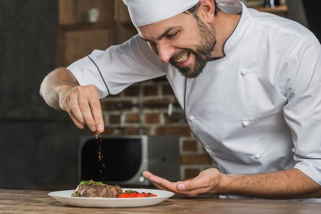 Sorrindo jovem tempero masculino especiarias sobre comida Foto gratuita