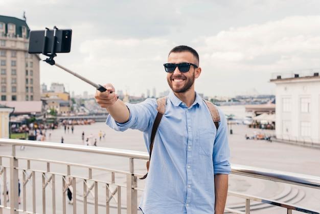 Sorrindo jovem usando óculos de sol tomando selfie com smartphone Foto gratuita