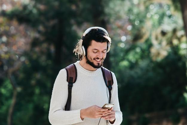 Sorrindo jovem usando telefone para ouvir música no fone de ouvido no parque Foto gratuita