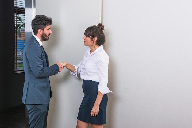 Sorrindo jovens empresários apertando as mãos Foto gratuita