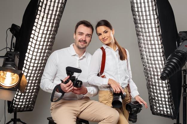 Sorrindo jovens fotógrafos profissionais posando no estúdio Foto Premium