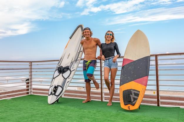 Sorrindo jovens surfistas ativos casal relaxando na praia após esporte com prancha de surf. estilo de vida saudável. esportes aquáticos extremos Foto Premium