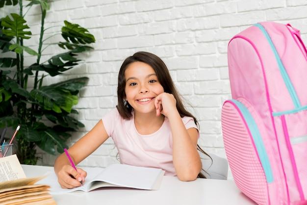 Sorrindo linda garota fazendo lição de casa em casa Foto gratuita