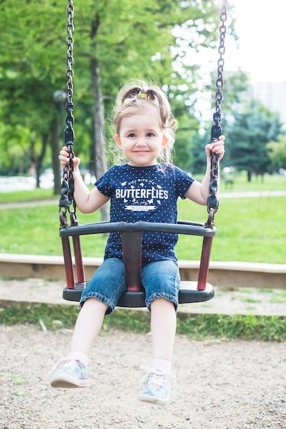 Sorrindo linda garota sentada no balanço no parque Foto gratuita