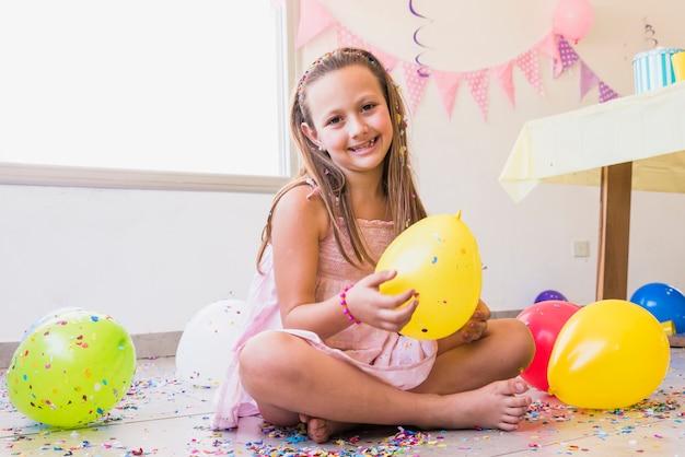 Sorrindo linda garotinha sentada no chão com confete e balões Foto gratuita