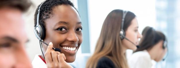 Sorrindo linda mulher afro-americana, trabalhando em call center com equipe diversificada Foto Premium