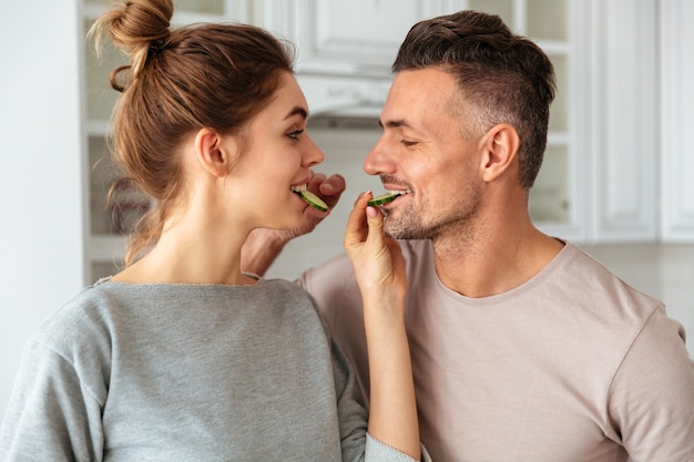 Sorrindo lindo casal cozinha juntos na cozinha e alimentando um ao outro Foto gratuita
