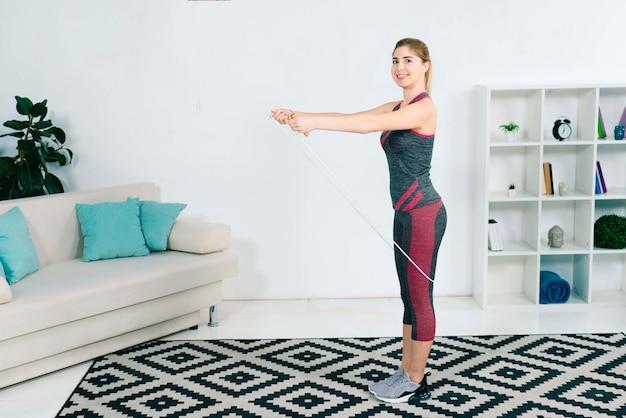 Sorrindo, loiro, mulher jovem, exercitar, com, pular corda, casa, em, a, sala de estar Foto gratuita