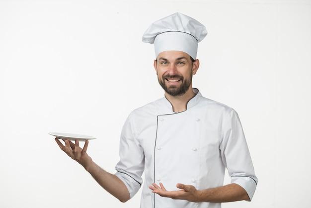 Sorrindo, macho, cozinheiro, apresentando, seu, prato, contra, branca, fundo Foto gratuita