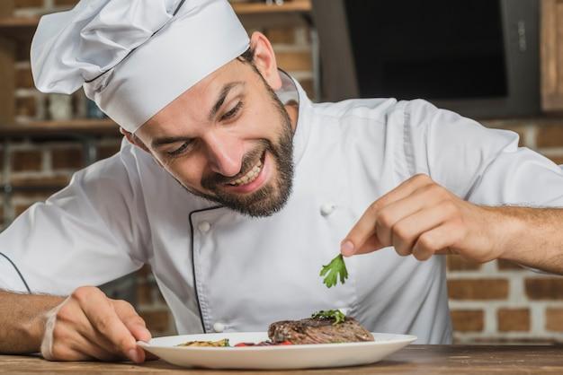 Sorrindo, macho, cozinheiro chefe, decorando, alimento, prato Foto gratuita