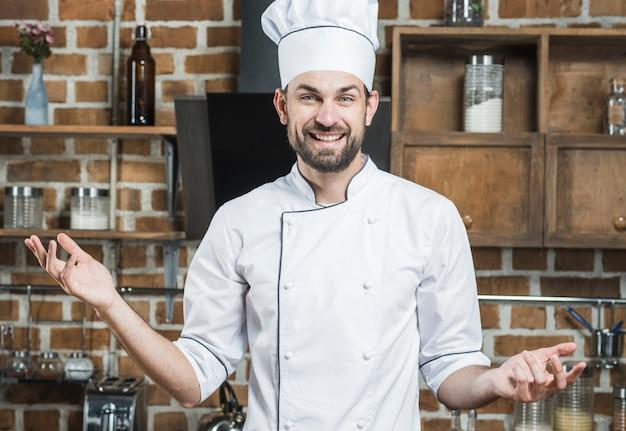 Sorrindo, macho, cozinheiro, ficar, em, cozinha, shrugging Foto gratuita
