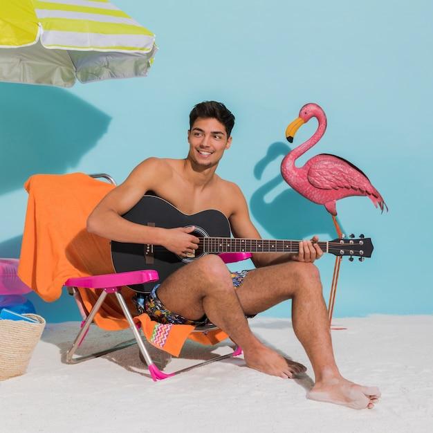 Sorrindo, macho jovem, violão jogo, em, estúdio Foto gratuita